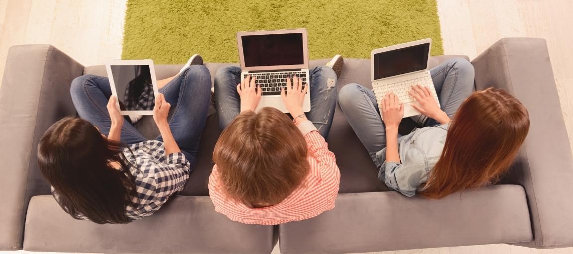 Vue de haut : 3 femmes assises sur un canapé avec un PC ou une tablette