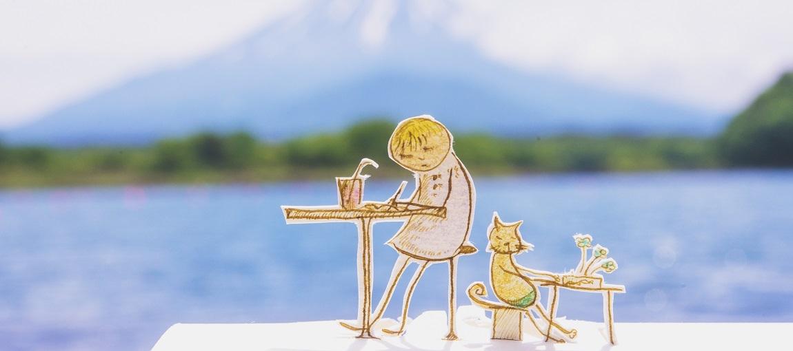 personnage (enfant+ animal) en papier en train d'écrire devant lac et montagne