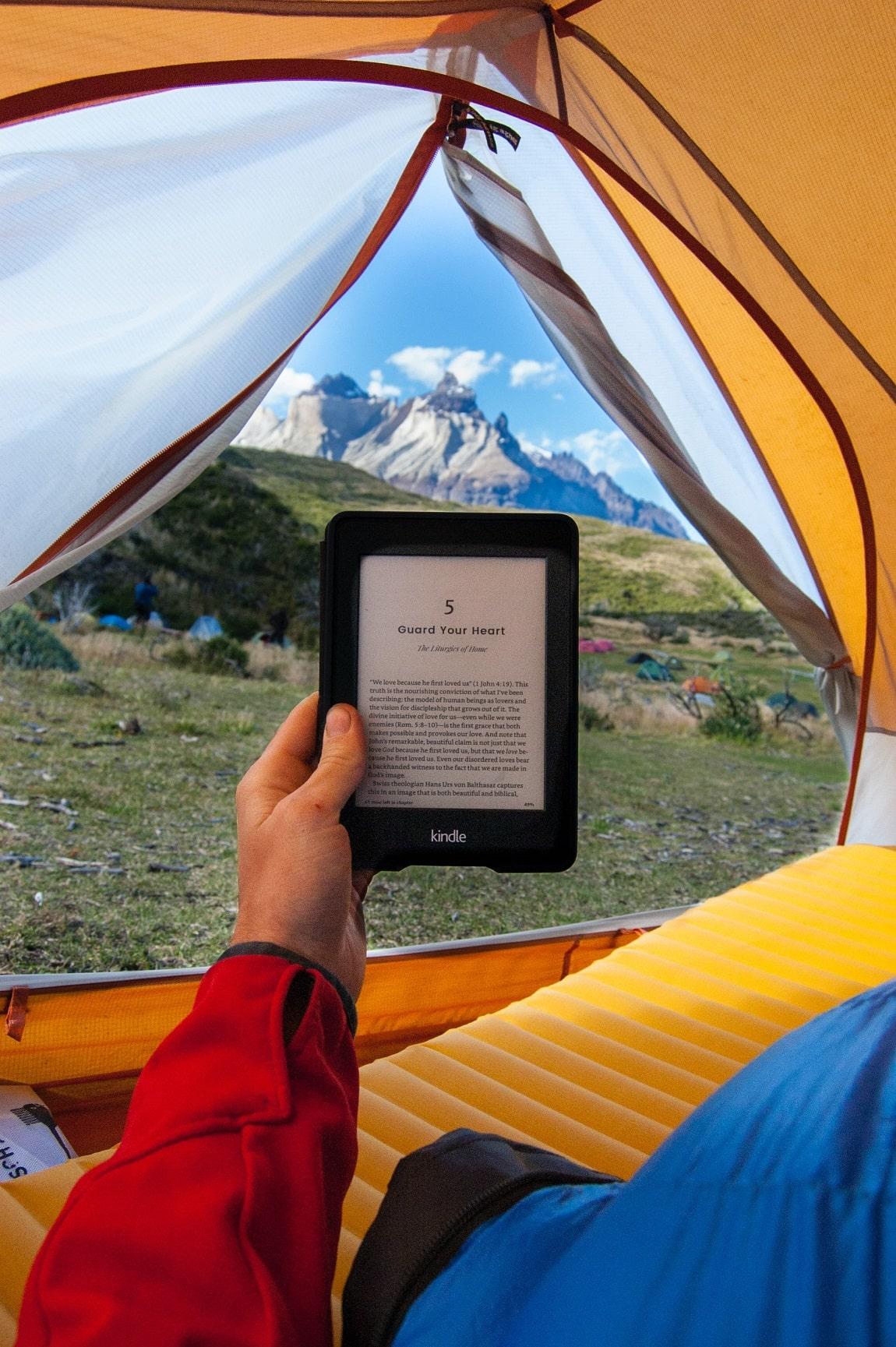 Liseuse dans une tente avec comme fond la montagne
