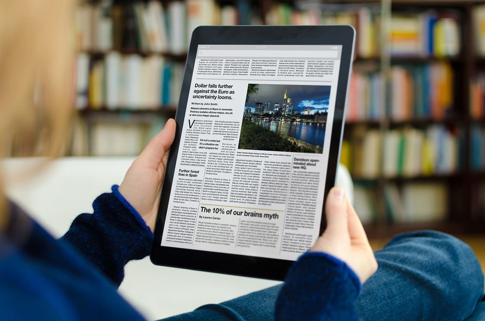femme lisant presse sur tablette