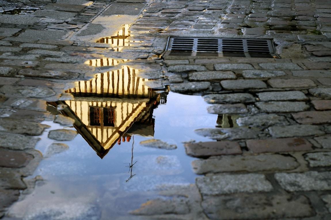Reflet d'une maison rouannaise ans une flaque -  5 lieux culturels à moins de 2h de Cergy