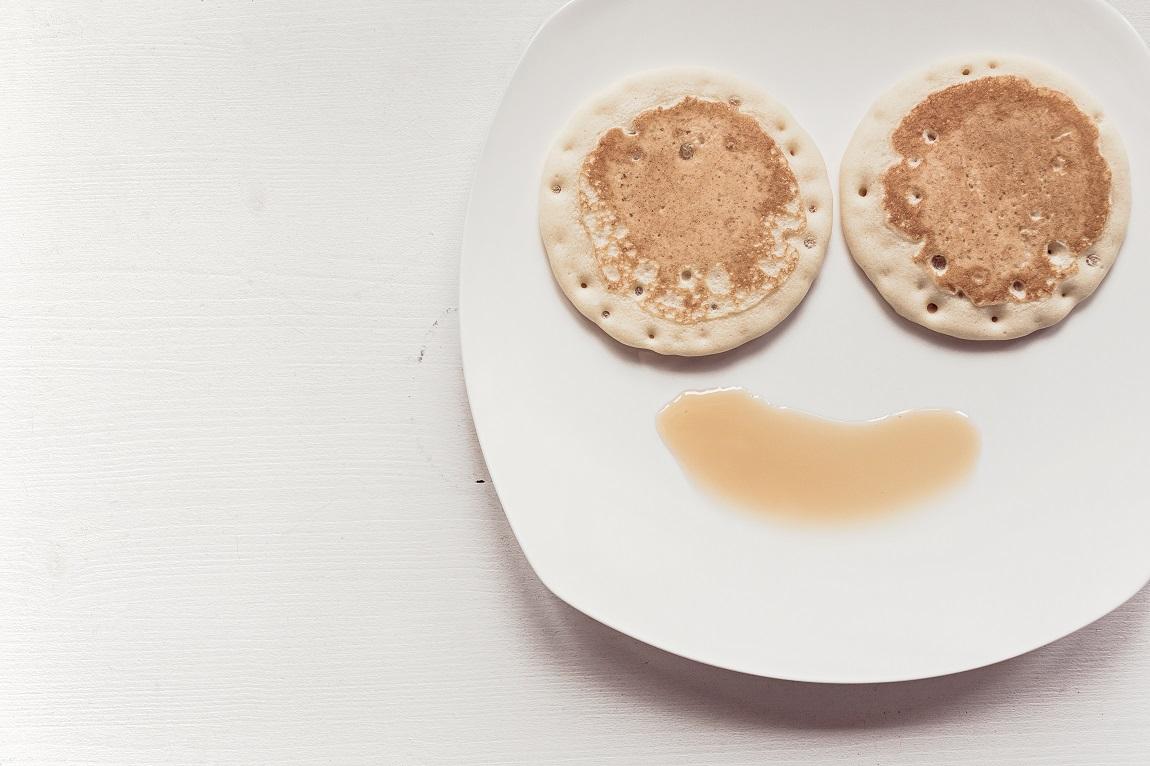 assiette représentant un visage avec panecakes pour les yeux et sirop d'érable pour la bouche