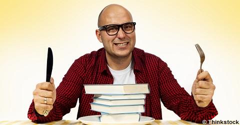 © Thinkstock - un homme, fourchette et couteau en main est attablé devant une pile de livre - livres gourmands - bibliothèques de Cergy-Pontoise